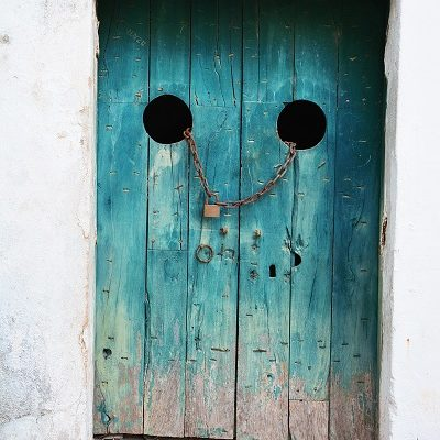 blue worn looking wooden door with chain and padlock
