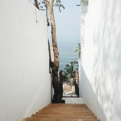 earthen staircase between white buildings leading to a waterfront